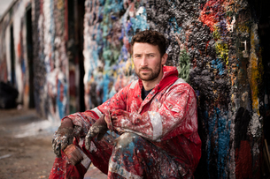 Portrait of male ship painter sitting against paint splattered wallの写真素材 [FYI03805002]