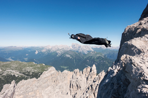 Wingsuit BASE jumper jumping from cliff, Italian Alps, Alleghe, Belluno, Italyの写真素材 [FYI03805004]