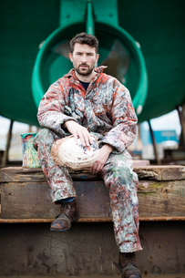 Portrait of male ship painter sitting in front of green ship hullの写真素材 [FYI03805011]