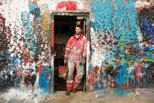 Male ship painter leaning against paint splattered doorwayの写真素材 [FYI03805014]