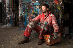 Portrait of male ship painter sitting against paint splattered wallの写真素材 [FYI03805016]