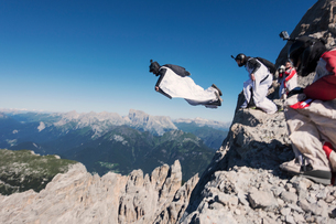 Wingsuit BASE jumping team jumping from cliff, Italian Alps, Alleghe, Belluno, Italyの写真素材 [FYI03805020]