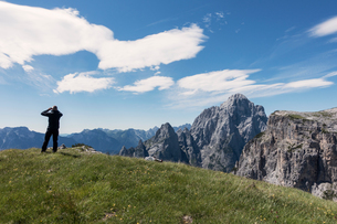 BASE jumper is checking the wind and clouds before walking to the cliff edge, Italian Alps, Alleghe,の写真素材 [FYI03805027]
