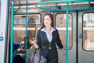 Businesswoman travelling in Docklands Light Railway train, Londonの写真素材 [FYI03805033]