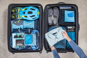 Overhead view of man's hands packing suitcase with walking boots, bike helmet, backpack, retro camerの写真素材 [FYI03805066]