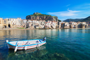 Fisherman's boat near old town waterfront and La rocca, Cefalu, Sicily, Italyの写真素材 [FYI03805069]