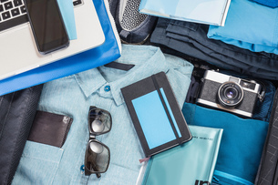 Overhead detail of packed suitcase with blue shirt,  retro camera, laptop, smartphone and notebookの写真素材 [FYI03805070]