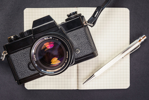 Overhead view of retro camera, notebook and penの写真素材 [FYI03805076]