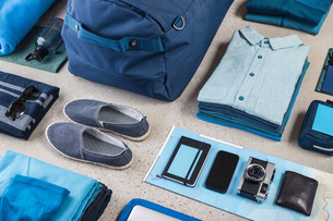 Overhead view of travel packing with blue shirt,  retro camera, training shoes, smartphone and notebの写真素材 [FYI03805081]