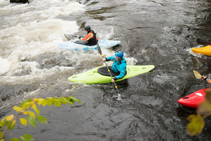 Male and female kayakers paddling to rapids on river Dee, Llangollen, North Walesの写真素材 [FYI03805089]