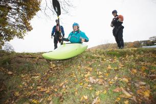 Female kayakers preparing to move down river bank in kayakの写真素材 [FYI03805101]