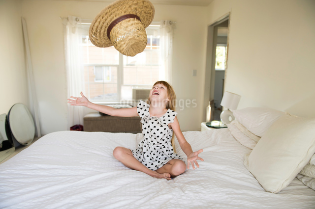 Young girl sitting on bed, throwing straw hat up in airの写真素材 [FYI03805133]