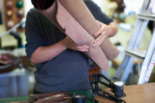 Male worker in leather workshop, carrying roles on leather, mid sectionの写真素材 [FYI03805169]
