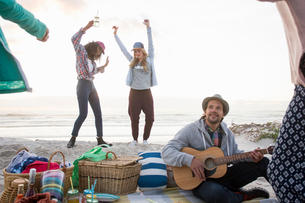 Young man playing guitar and female friends dancing at beach, Cape Town, Western Cape, South Africaの写真素材 [FYI03805193]