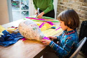 Mother and son decorating pinata at homeの写真素材 [FYI03805213]