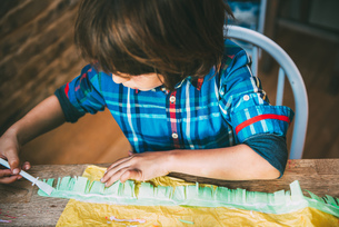 Boy spreading glue on crepe paper to make pinataの写真素材 [FYI03805215]