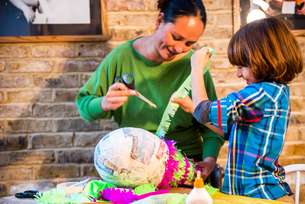 Mother and son decorating pinata at homeの写真素材 [FYI03805216]