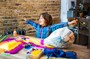 Boy decorating pinata at homeの写真素材 [FYI03805217]