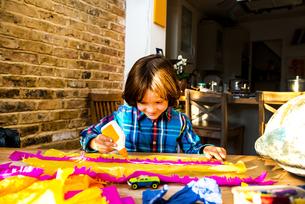 Boy spreading glue on crepe paper to make pinataの写真素材 [FYI03805218]