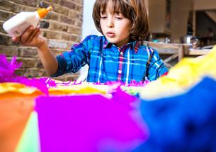 Boy spreading glue on crepe paper to make pinataの写真素材 [FYI03805219]