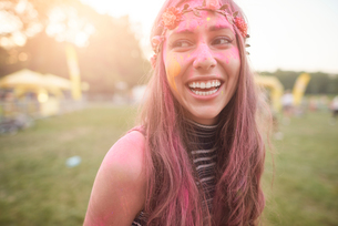 Portrait of young woman at festival, covered in colourful powder paintの写真素材 [FYI03805222]