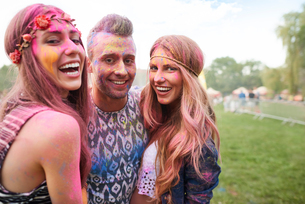 Group of friends at festival, covered in colourful powder paintの写真素材 [FYI03805228]