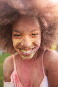Portrait of young woman at festival, covered in colourful powder paintの写真素材 [FYI03805229]