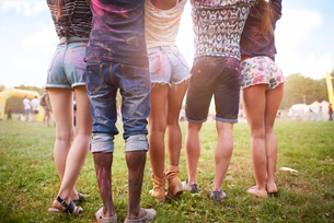 Group of friends at festival, covered in colourful powder paint, low section, rear viewの写真素材 [FYI03805232]