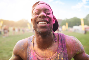 Portrait of young man at festival, covered in colourful powder paintの写真素材 [FYI03805237]