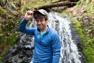 Man in front of waterfall wearing baseball cap looking at camera smilingの写真素材 [FYI03805247]