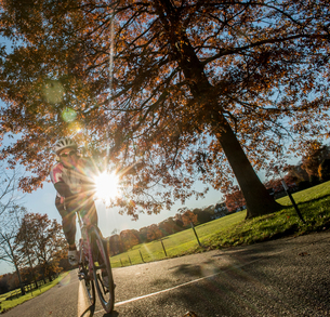 Angled view of cyclist cycling in sunlightの写真素材 [FYI03805259]