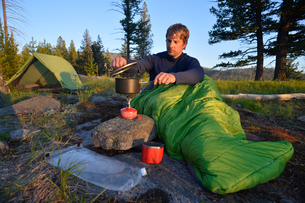 Male camper in sleeping bag prepares a meal on camping stove at Midnight Ridge, Colville National Foの写真素材 [FYI03805301]