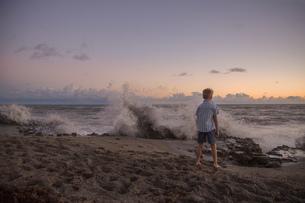 Rear view of boy watching splashing waves at sunrise, Blowing Rocks Preserve, Jupiter Island, Floridの写真素材 [FYI03805309]