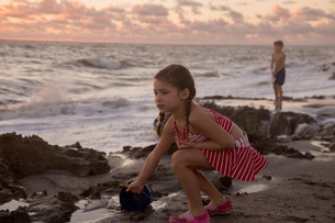 Girl filling toy bucket on beach at sunrise, Blowing Rocks Preserve, Jupiter Island, Florida, USAの写真素材 [FYI03805320]