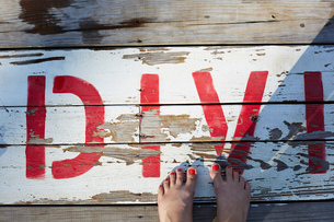 Woman's feet on wooden boards, overhead viewの写真素材 [FYI03805407]