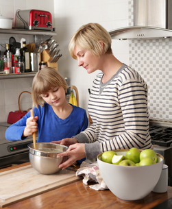 Mother and daughter in kitchen preparing foodの写真素材 [FYI03805415]