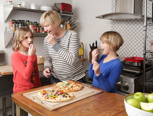 Mother and two daughters in kitchen preparing food, nibbling on ingredientsの写真素材 [FYI03805421]