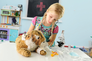 Girl pretending to be vet examining toy tiger using stethoscopeの写真素材 [FYI03805458]