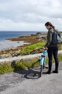 Young woman standing with bicycle beside sea wall, Inishmore, Irelandの写真素材 [FYI03805627]