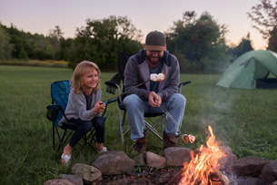 Father and daughter sitting beside campfire, toasting marshmallows over fireの写真素材 [FYI03805653]