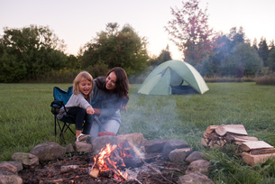 Mother and daughter sitting beside campfire, cooking sausage over fireの写真素材 [FYI03805659]