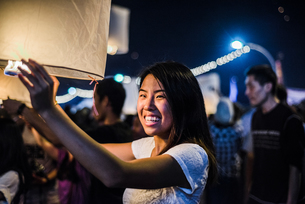 Young woman holding lit paper lantern waiting to release at Loy Krathong Paper Lantern Festival in Cの写真素材 [FYI03805687]