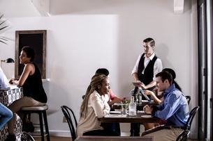 Waiter serving diners in restaurantの写真素材 [FYI03805741]