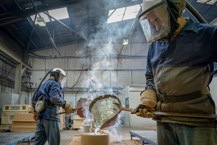 Workers pouring molten aluminium into moulds in precision casting factoryの写真素材 [FYI03805805]