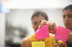 Two businesswomen removing sticky note from office glass wallの写真素材 [FYI03805847]