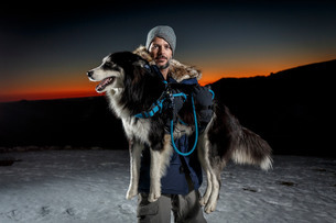 Portrait of mature man carrying dog in snow at nightの写真素材 [FYI03805874]