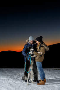 Couple playing with dog in snow at nightの写真素材 [FYI03805876]