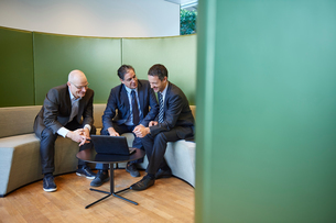 Three businessmen meeting on office sofaの写真素材 [FYI03805940]
