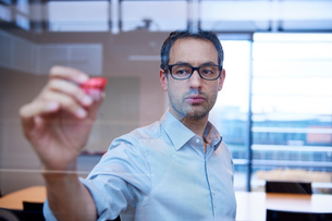 Businessman making presentation drawing graph on office windowの写真素材 [FYI03805943]