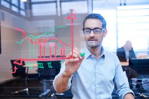 Businessman making presentation drawing graph on office windowの写真素材 [FYI03805956]